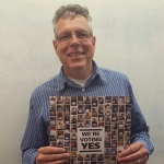 a photo of paul dannenfelser smiling and holding up a poster with the faces of many adjuncts on it with the message we are voting yes